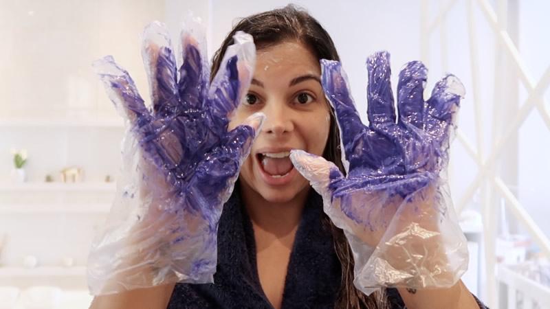 Evelyn Regly mostra a luva com a máscara da liberdade durante a aplicação no chuveiro.